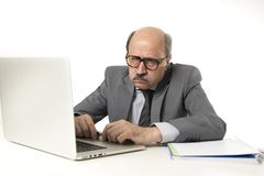 Hogere rijpe bezige bedrijfsmens met kaal hoofd bij zijn jaren '60 werken beklemtoond en gefrustreerd bij laptop van de bureaucom Royalty-vrije Stock Fotografie