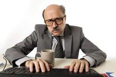 Hogere rijpe bezige bedrijfsmens met kaal hoofd bij zijn jaren '60 werken beklemtoond en gefrustreerd bij laptop van de bureaucom stock afbeeldingen