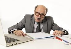 Hogere rijpe bezige bedrijfsmens met kaal hoofd bij zijn jaren '60 werken beklemtoond en gefrustreerd bij laptop van de bureaucom stock foto