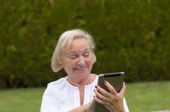 Hogere rustige vrouw die een zwarte tabletpc met behulp van royalty-vrije stock foto's