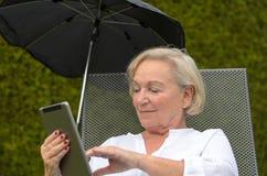Hogere rustige vrouw die een zwarte tabletpc met behulp van stock fotografie