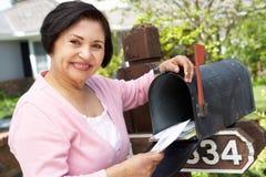 Hogere Spaanse Vrouw die Brievenbus controleren royalty-vrije stock afbeeldingen