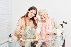 Hogere spelen met een zorg hulpdomino Royalty-vrije Stock Fotografie