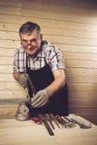 Hogere timmerman die in zijn workshop werken Stock Afbeeldingen