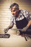 Hogere timmerman die in zijn workshop werken Royalty-vrije Stock Foto