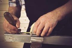 Hogere timmerman die in zijn workshop werken Stock Afbeelding