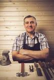 Hogere timmerman die in zijn workshop werken stock foto's