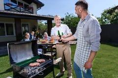 Hogere vader en volwassen zoon het drinken bier terwijl in openlucht het roosteren van vlees stock afbeeldingen