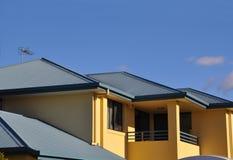Hogere verdieping van teruggegeven huis met metaaldak Stock Foto's