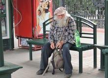 Hogere volwassen mensenzitting op de bank van een bushalte Stock Foto's
