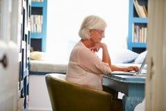 Hogere Vrouw bij Bureau die in Huisbureau werken met Laptop Stock Afbeeldingen