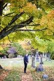 Hogere vrouw bij graf in begraafplaats royalty-vrije stock afbeelding
