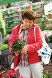 Hogere vrouw in bloemwinkel royalty-vrije stock foto
