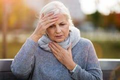 Hogere vrouw die aan een hoofdpijn lijdt royalty-vrije stock foto