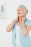 Hogere vrouw die aan halspijn lijden in medisch bureau Royalty-vrije Stock Foto's