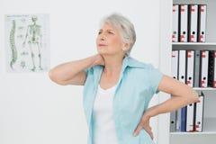 Hogere vrouw die aan halspijn lijden in medisch bureau Stock Foto