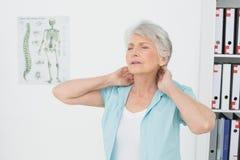 Hogere vrouw die aan halspijn lijden in medisch bureau Stock Foto's
