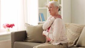 Hogere vrouw die aan halspijn thuis lijden stock videobeelden