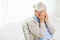 Hogere vrouw die aan hoofdpijn of zorg lijden Stock Fotografie