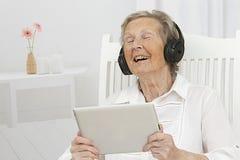 Hogere vrouw die aan muziek op haar tablet met hoofdtelefoons luisteren Stock Foto