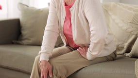 Hogere vrouw die aan pijn in been thuis lijden stock video
