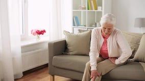 Hogere vrouw die aan pijn in been thuis lijden stock videobeelden