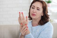 Hogere vrouw die aan pijn in de verbindingen van de hand bij ho lijden stock foto