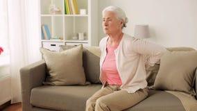 Hogere vrouw die aan pijn in rug thuis lijden stock video