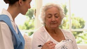 Hogere vrouw die aan verpleegster spreken stock footage