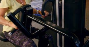 Hogere vrouw die achteroefening op machine 4k doen stock footage