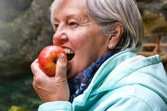 Hogere vrouw die appel buiten in het park eten stock afbeeldingen
