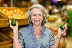 Hogere vrouw die avocado twee houden stock foto's