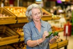 Hogere vrouw die avocado twee houden royalty-vrije stock foto