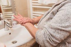 Hogere vrouw die in badjas handroom in badkamers, close-up toepassen royalty-vrije stock foto