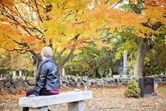 Hogere vrouw die in begraafplaats rouwen stock afbeeldingen