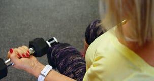 Hogere vrouw die bicepsentraining met domoor in geschiktheidsstudio 4k doen stock footage