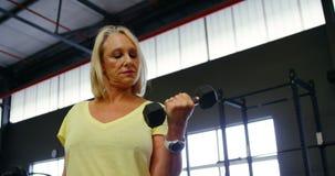Hogere vrouw die bicepsentraining met domoor 4k doen stock videobeelden