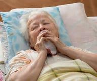 Hogere vrouw die bij bed liggen Stock Foto's