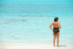 Hogere vrouw die blauwe trillende oceaan bekijkt stock afbeeldingen
