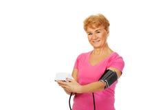 Hogere vrouw die bloeddruk met automatische manometer meten Royalty-vrije Stock Fotografie