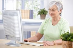 Hogere vrouw die computer thuis met behulp van Royalty-vrije Stock Afbeeldingen
