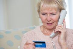 Hogere Vrouw die Creditcarddetails op de Telefoon geven Royalty-vrije Stock Foto