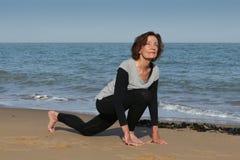 Hogere vrouw die de begroeting van de yogazon op het strand doen Royalty-vrije Stock Foto