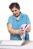 Hogere vrouw die de kleren vouwt stock afbeelding