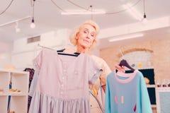 Hogere vrouw die de kleren in de winkel kiezen royalty-vrije stock afbeelding