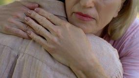 Hogere vrouw die de mens na slecht nieuws over ziekte of verlies, familiesteun omhelzen stock fotografie