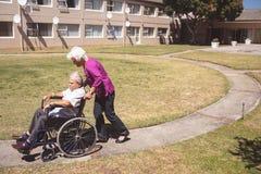 Hogere vrouw die de hogere mens op rolstoel duwen bij verzorgingspark stock foto