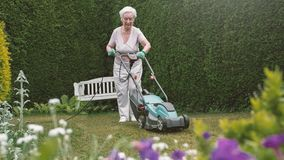 Hogere vrouw die in de tuin met maaimachine werken royalty-vrije stock fotografie