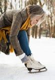 Hogere vrouw die in de winterkleren op oude schaatsen zetten stock afbeeldingen