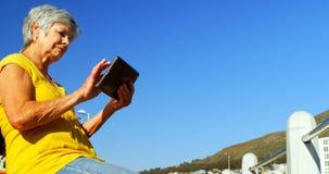 Hogere vrouw die digitale tablet gebruiken bij promenade 4k stock videobeelden